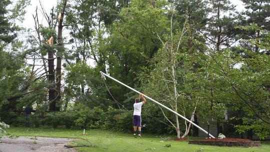 A teen steadies a flagpole bent by storms in the 1700 block of Grandview Road in Alexandria Monday.