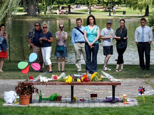 "People pause by a bench at Boston's Public Garden, Tuesday, Aug. 12, 2014, where a small memorial has sprung up at the place where Robin Williams filmed a scene during the movie, ""Good Will Hunting."" Williams, 63, died at his San Francisco Bay Area home Monday in an apparent suicide."
