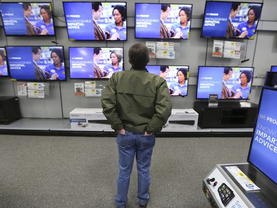 A customer checks out the flat screen televisions while shopping at Best Buy in West Des Moines. The company announced Monday that it would close its store on Southeast 14th Street in Des Moines this summer.