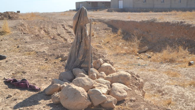 A makeshift memorial made of stones is the only sign marking a Yazidi mass grave in northern Iraq.