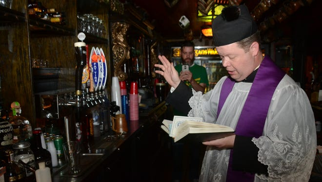 The Rev. Chad Partain says a blessing over the beer taps at Finnegan's Wake last year.
