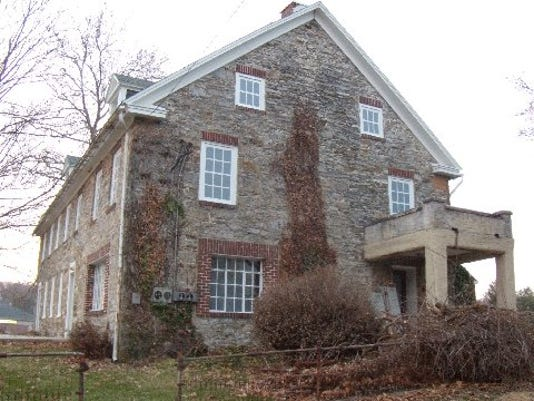 The east end of the painted Hoke House with window coverings on and vines and brush being cleared.