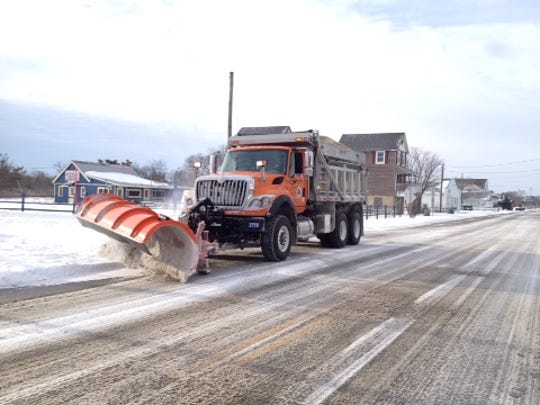 A state snow plow drives down Savannah Road in Lewes after a January 2014 storm.