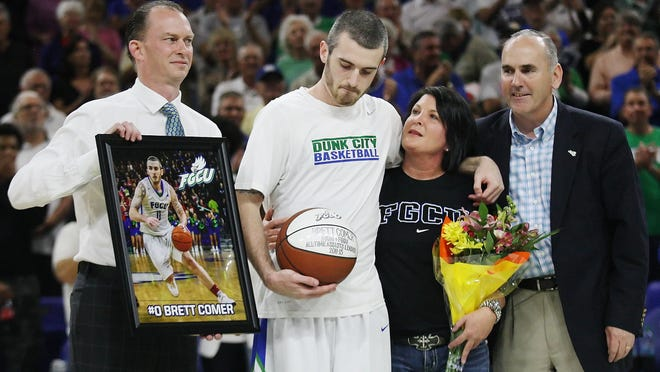 FGCU's Brett Comer, center, holds back tears while being honored Wednesday at Alico Arena in Fort Myers. Coach Joe Dooley, left, Comer's mother, Heather Comer and athletic director Ken Kavanaugh are with Comer.