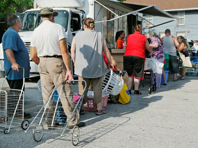 Toting baskets or bags, or even pulling carts, people line up Saturday for free food at the mobile pantry provided by Food Finders Food Bank in the Journal & Courier parking lot at Sixth and Ferry streets.