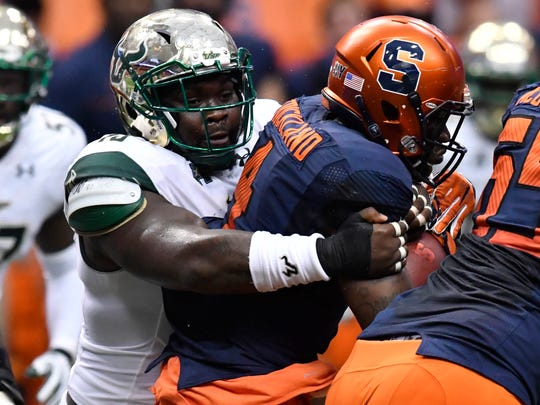Sep 17, 2016; Syracuse, NY, USA; South Florida Bulls defensive tackle Deadrin Senat (10) makes a tackle on Syracuse Orange running back Dontae Strickland (4) during the first quarter of a game at the Carrier Dome.