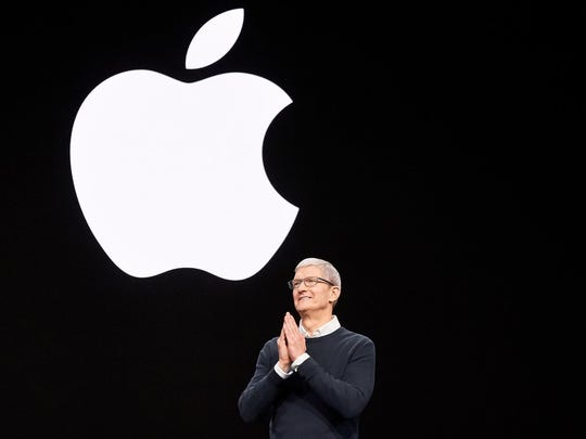 CEO Tim Cook on stage in front of the Apple logo.