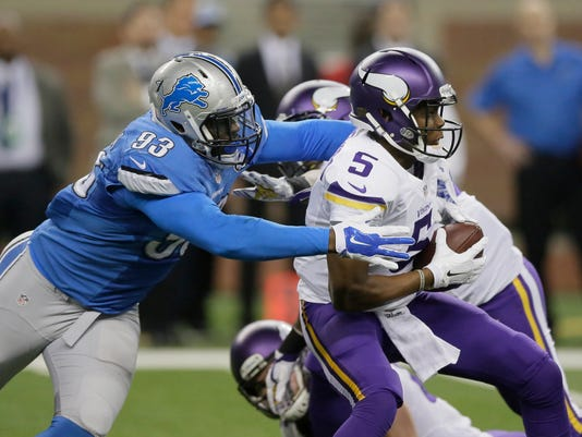 Minnesota Vikings quarterback Teddy Bridgewater (5) pulls away from Detroit Lions defensive end George Johnson (93) during the first half of an NFL football game in Detroit, Sunday, Dec. 14, 2014. (AP Photo/Duane Burleson)