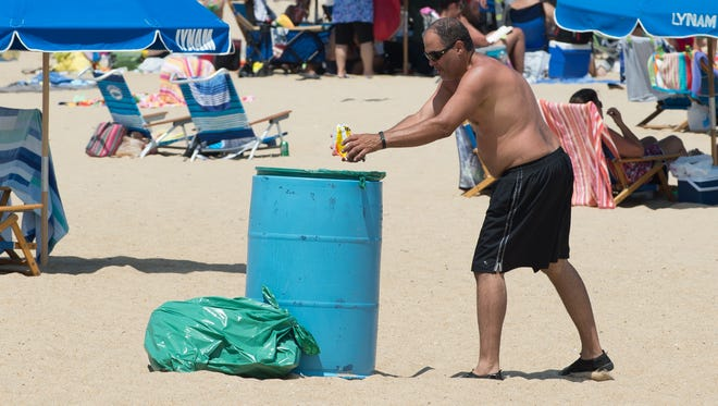 Luis Ortiz of Bushkill, Pa., throws away trash into a trash can on the beach at Rehoboth Beach.