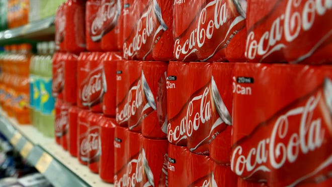 Packaged cans of Coca-Cola Co. soda are displayed for sale at an E-Mart Co. store, a subsidiary of Shinsegae Co., in Incheon, South Korea, on Saturday, Dec. 21, 2013.