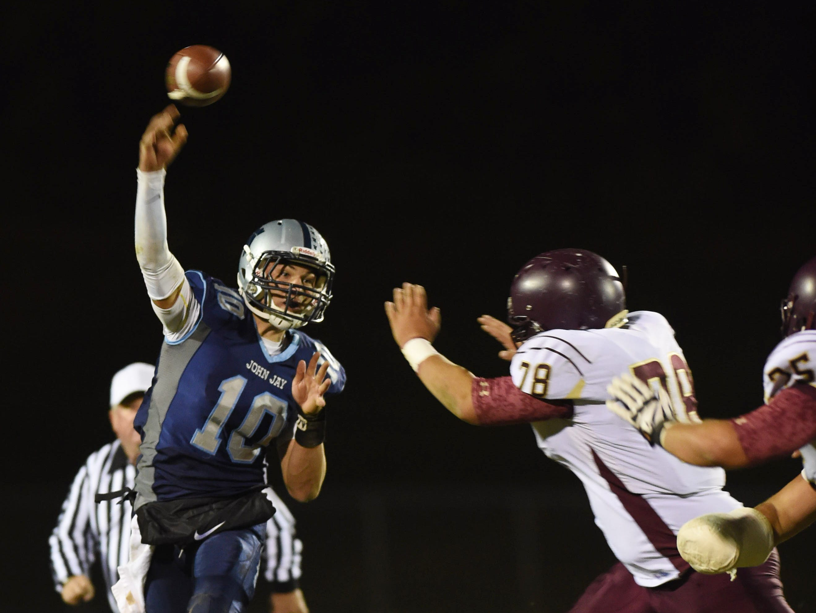 John Jay's Ryan Schumacher passes the ball as Arlington's Jordan Valerious closes in on him during Friday's game in Wiccopee.