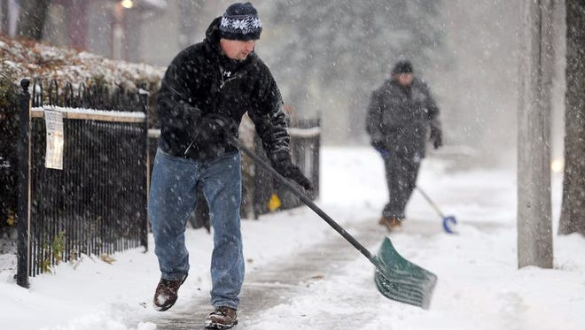 Casey Degerstrom of Minneapolis clears a sidewalk as he tries to keep up with the snow.