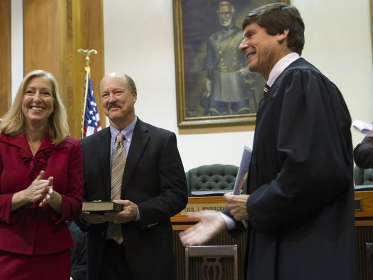 Chief Judge Ray Rosman, right, swears in Linda Doggett,