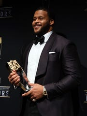 The Rams' Aaron Donald holds his Defensive Player of the Year award on Saturday night.