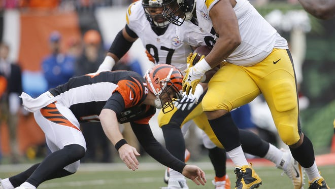 Cincinnati Bengals quarterback Andy Dalton (14) tackles Pittsburgh Steelers defensive end Stephon Tuitt (91) after Tuitt intercepted a pass in the first quarter during the Week 14 NFL football game between the Pittsburgh Steelers and the Cincinnati Bengals, Sunday, Dec. 13, 2015, at Paul Brown Stadium in Cincinnati. The Steelers led 16-7 at halftime. Dalton left the game with an injury on this play.