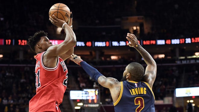 Chicago Bulls forward Jimmy Butler shoots over the defense of Cleveland Cavaliers guard Kyrie Irving (2) during the second half at Quicken Loans Arena. Butler had a triple-double as the Bulls won 117-99.