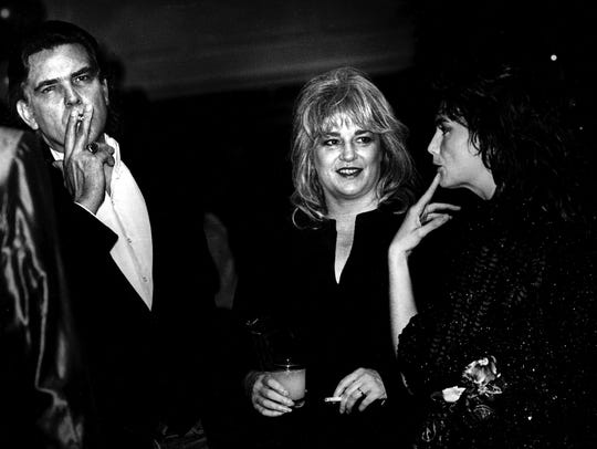 Guy Clark, left, Susanna Clark and Emmylou Harris talk during one of the parties in Nashville during 1985 CMA week.