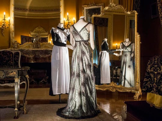 """A dress worn by Lady Mary Crawley """"Downton Abbey"""" season 1 stands alongside a traditional lady's maid dress in Mrs. Vanderbilt's bedroom at Biltmore for a monthslong costume exhibit opening Feb. 5."""