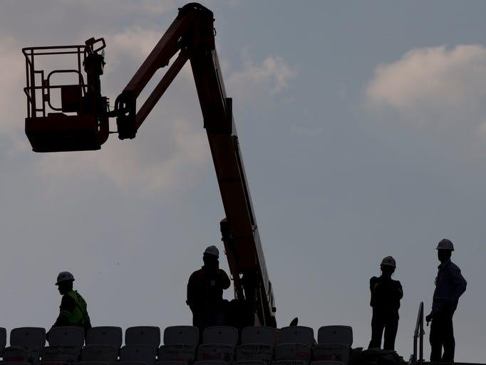 Men work on the Itaquerao stadium in Sao Paulo, Brazil, Thursday, May 8, 2014.