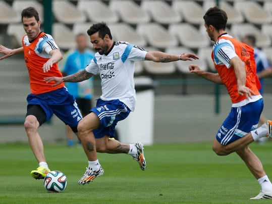 Argentina's Ezequiel Lavezzi, center, and Jose Maria Basanta, left, vie for the ball as Martin Demichelis, right, looks on during a training session in Vespasiano, near Belo Horizonte, Brazil, Thursday, June 12, 2014. Argentina will play in group F of the Brazil 2014 soccer World Cup. (AP Photo/Victor R. Caivano)