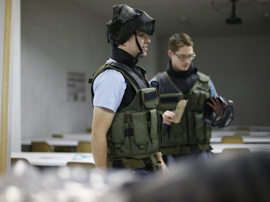 Students Jacob Pewitt, center, and Joe Clements gear up before the physical training portion of the  tactical operations class at the Tallahassee Indoor Shooting Range on Saturday