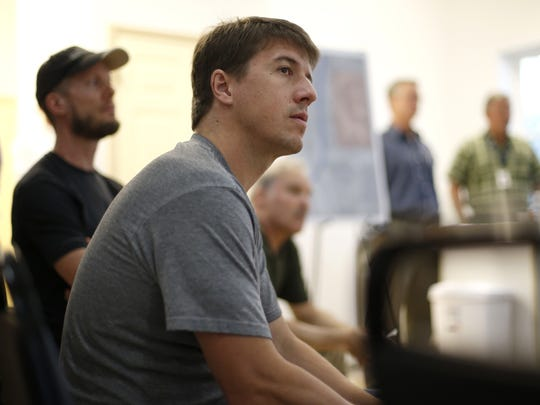1200 Stearns St. resident Casey Rychlik listens to Zimmer Development Company representatives at a Thursday meeting. The developer plans to build a new student housing complex that residents fear will take away the natural beauty of their neighborhood.