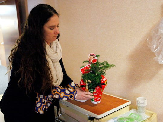 Terri McCook-Guerrero places a Christmas tree on her son's bedside table in a rehabilitation center Dec. 23. Anthony Leyva, 22, was riding his bicycle home on Hendersonville Road in the early morning of Nov. 20 when he was struck from behind by an SUV.