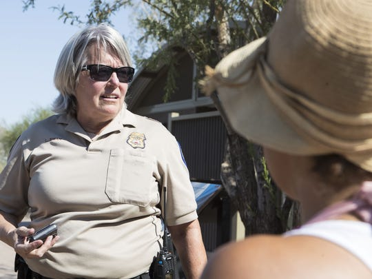 Lynn Swan, park ranger supervisor, speaks to Erika Pinci about the heat and the importance of bringing water on the Echo Canyon Trail at Camelback Mountain in Phoenix on June 18, 2017.
