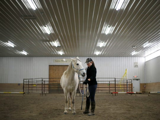 University of Toledo occupational therapy student Sarah Hayes works with Lil Sis as part of her program capstone project at Cincinnati Therapeutic Riding and Horsemanship in Miami Township, Ohio, on Friday, Feb. 2, 2018.
