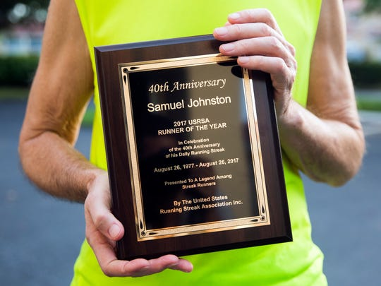 Sam Johnston, 75, holds his Runner of the Year plaque outside of his home on Tuesday, September 5, 2017 in North Naples. Johnston runs every morning and just eclipsed the forty year mark of running everyday without taking a day off as verified by the United States Running Streak Association.