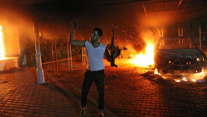 BenAn armed man waves his rifle as buildings and cars are engulfed in flames after being set on fire inside the US consulate compound in Benghazi, Libya  late on Sept. 11, 2012.