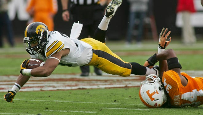 Iowa Hawkeyes running back Jordan Canzeri (33) dives for extra yardage as he is tripped up by Tennessee Volunteers linebacker Jalen Reeves-Maybin (34) in the first quarter of the TaxSlayer Bowl. Canzeri gained 120 yards in just 12 carries,