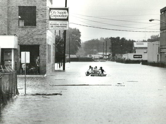 A group of people canoe through downtown Des Moines on Tuesday, July 13, 1993.