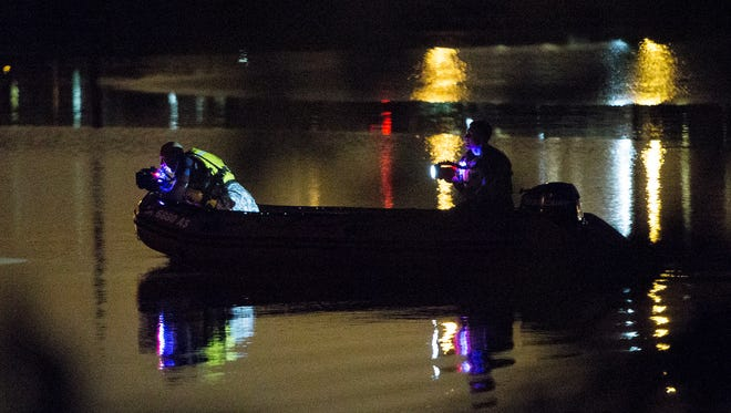 Cedar Rapids firefighters search Cedar Lake while looking for a teenager who was swept into a storm drain on Monday, June 30, 2014.