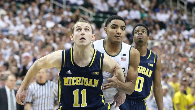 Nik Stauskas #11 and Derrick Morgan Jr #10 of the Michigan Wolverines defend against Gary Harris #14 of the Michigan State Spartans at Breslin Center on January 25, 2014 in East Lansing, Michigan.