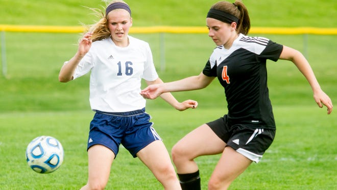 Regina's Sarah Lehman and Solon's Emma Moss work for the ball during the Regals game against the Spartans at Regina in Iowa City, IA on Tuesday, May 27, 2014.