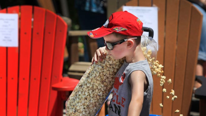 Aidan Schleyer, 5, of Chili loses some of his popcorn as he gets out of his wagon at the annual Fairport Canal Days on Saturday.