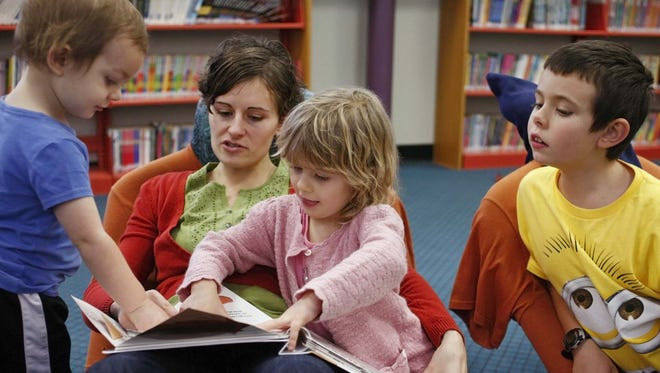 Annalise Jones reads with her children, Taylor (left), 2, Elisabeth (second from right), 5, and Rychen (right), 8, at the Salem Public Library on Friday, Dec. 27, 2013. The library has many activities to occupy children over the summer.