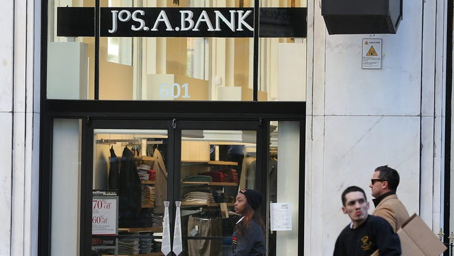 People walk past a Jos. A. Bank retail store on Dec. 5, 2013, in San Francisco.