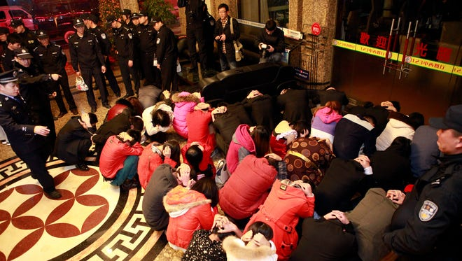Chinese policemen detain a group of suspects during a prostitution raid at a hotel in Dongguan in south China's Guangdong province on Feb. 9.