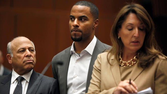 Former NFL football player Darren Sharper, center, shown here in a previous court appearance, is charged with two rapes in Los Angeles.