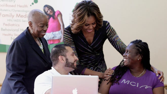 First lady Michelle Obama talks to Affordable Care Act enrollee Kalenthia Nunnally, right, as Annie Neasman, left,  and certified application counselor Paul Andres Salazar, second from left, look on at the Jessie Trice Community Health Care Center in Miami on March 5, 2014.