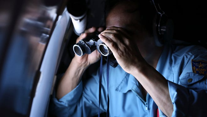 Vietnamese Air Force Col. Pham Minh Tuan searches for the missing Malaysia Airlines flight MH370 from a plane in the Gulf of Thailand on Thursday.