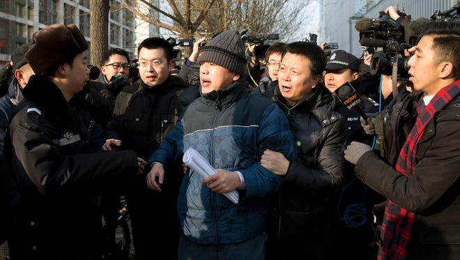 Zhang Qingfang, center, lawyer of legal scholar and founder of the New Citizens Movement Xu Zhiyong, is taken away by policemen as he speaks to the media near the No. 1 Intermediate People's Court in Beijing on Jan. 26, 2014.