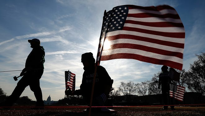 """Military veterans set up 1,892 American flags on the National Mall on March 27 in Washington, D.C. The Iraq and Afghanistan Veterans of America installed the flags to represent the 1,892 veterans and service members who committed suicide this year as part of the """"We've Got Your Back: IAVA's Campaign to Combat Suicide."""""""