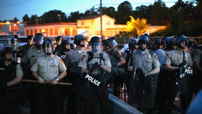 Police stand watch as demonstrators protest the shooting death of teenager Michael Brown in Ferguson, Mo. Brown was shot and killed by a Ferguson police officer on Saturday.