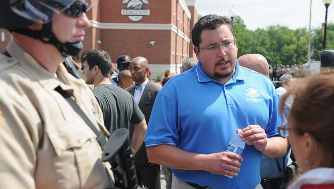 In Ferguson, Mo., Mayor James Knowles III, center, speaks to protesters outside the police department on Aug. 11.