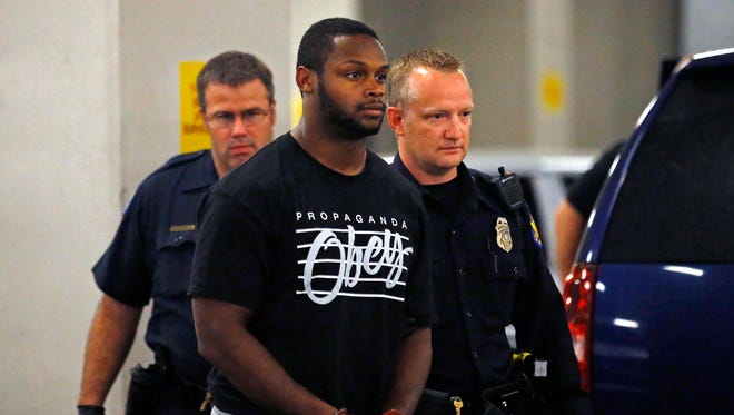 Phoenix police officers escort Arizona Cardinals running back Jonathan Dwyer, 25,  to the 4th Avenue Jail following his arrest.