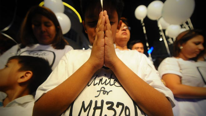 A young Malaysian boy prays for the missing Malaysia Airline Flight 370 in a photo from March. Searchers are resuming the hunt for the missing plane.