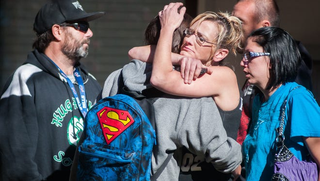 A Sparks Middle School student, back to camera, cries with family members after being released from Agnes Risley Elementary School Oct. 21 in Sparks Nev., after a shooting at Sparks Middle School.